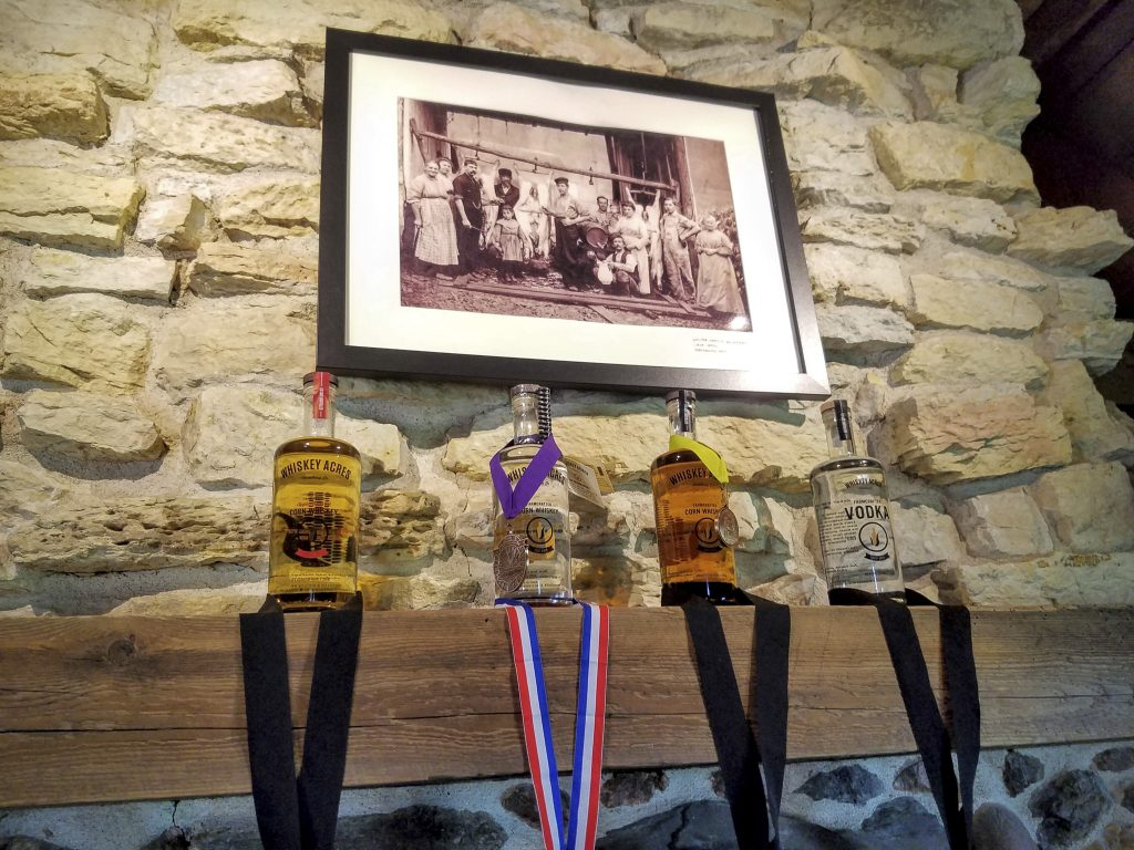 Bottles displayed with their numerous awards. Above is an authentic family photo of Jim's great grandmother and great grandfather.