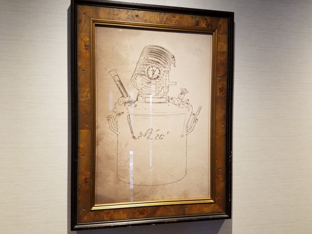 A sample of the whiskey still artwork hanging from the walls of Baptiste & Bottle.