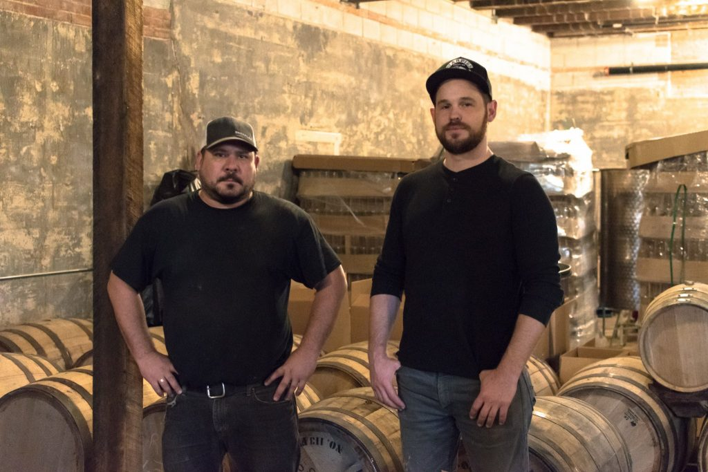 Micah Kibodeaux (left) and Andrew Howell (right) standing among barrels at Soltis Family Spirits